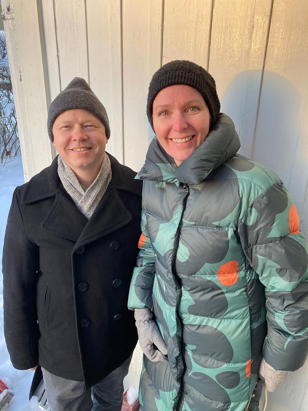 Armin Seebass ja Kristiina Aatsing poseeraavat kameralle hymyillen aurinkoisena talvipäivänä vaalean lankkutaustan edessä