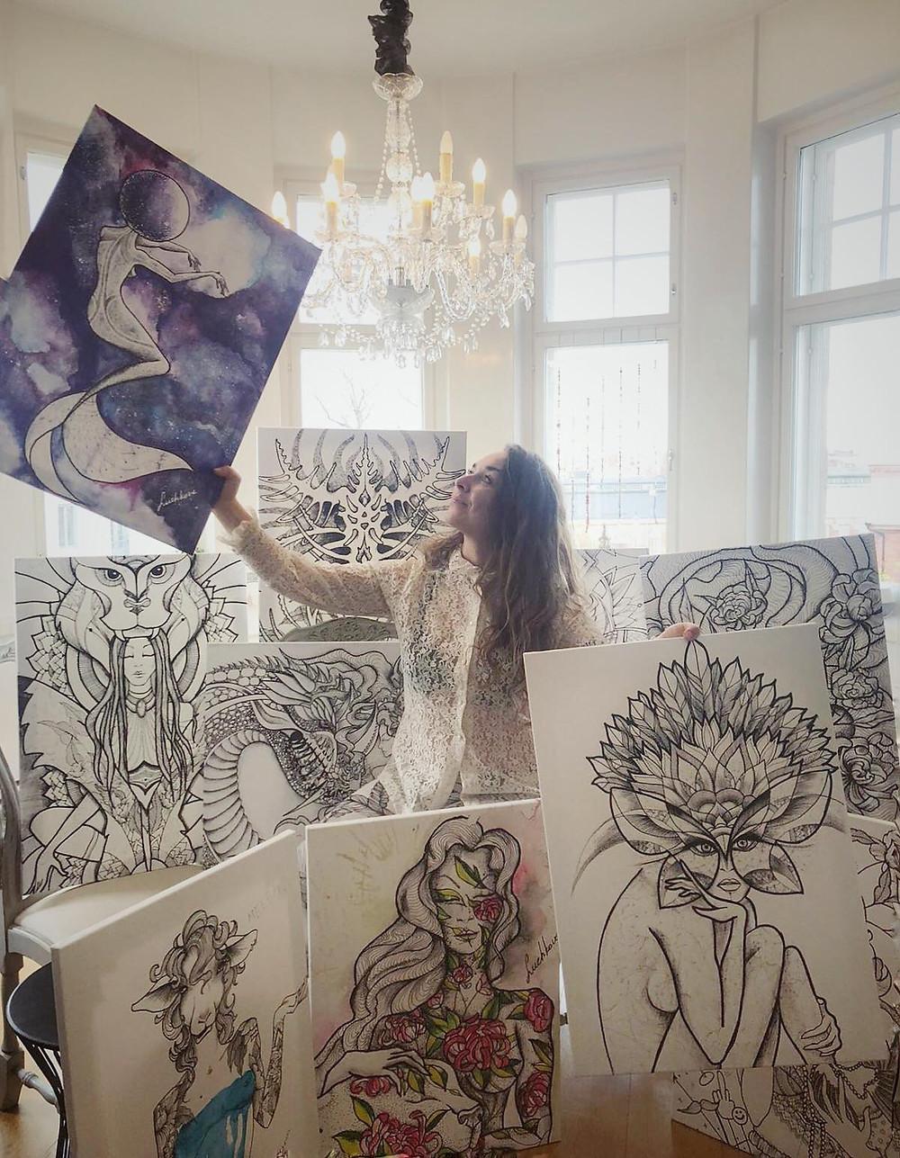 Sasha Luchkova kuvattuna taideteostensa keskellä, piirroksia naishahmoista. Kuvassa ateljee-tyyppinen huone, jossa taustalla isot ikkunat ja katossa suuri kattokruunu. Vaalea kuva.