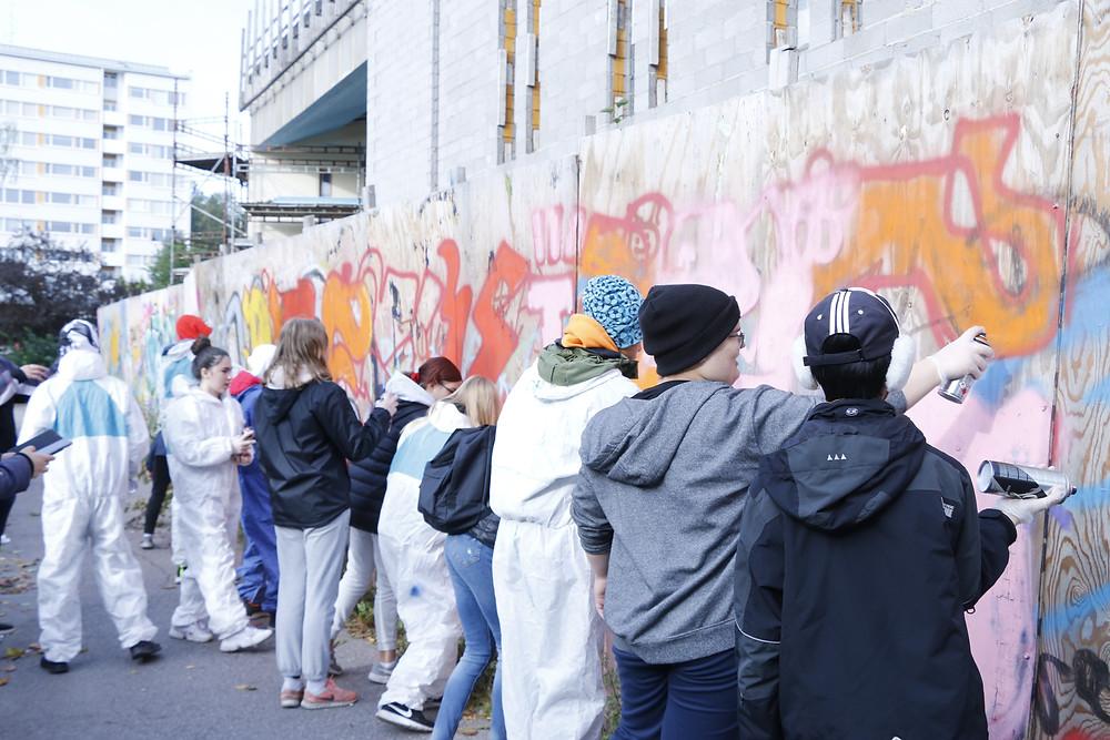 Lapset piirtävät graffiteja pahviseinään