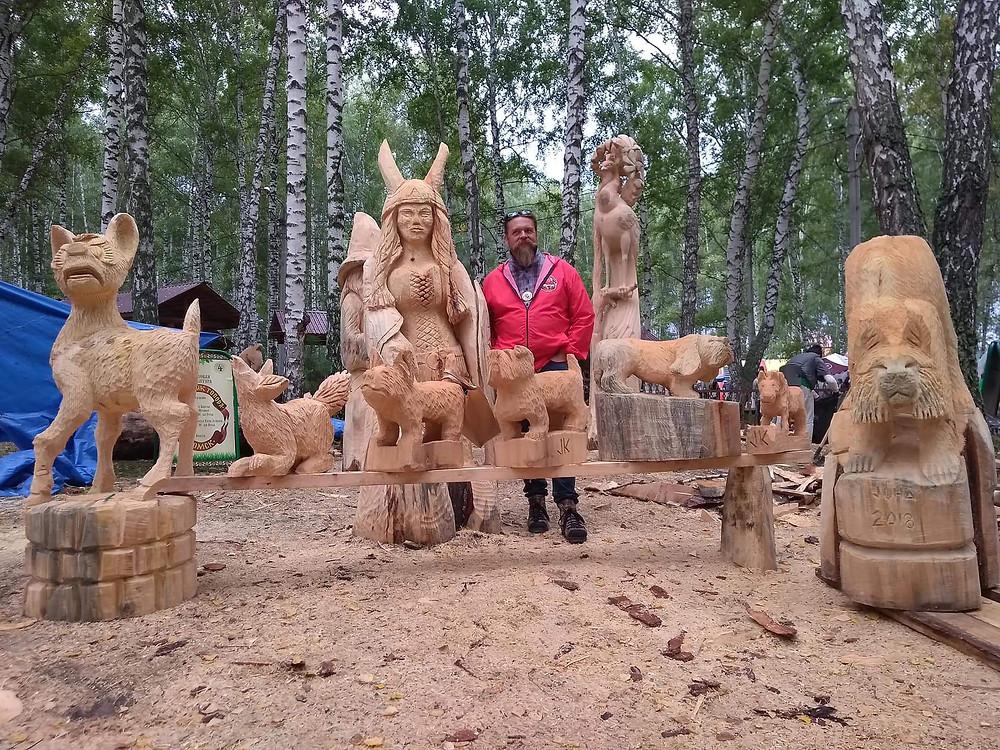 Juha Käkelä kuvattuna moottorisahataiteensa keskellä. Taideteoksista esillä erilaisia puusta moorrotisahalla veistettyjä eläimiä sekä viininkihahmo.