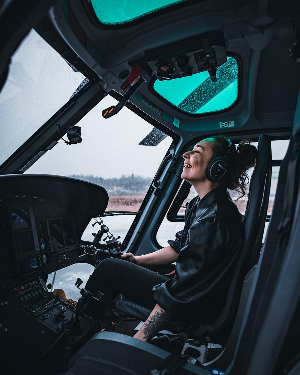 Sasha Luchkova istuu nauraen helikopterissa apukuskin paikalla.