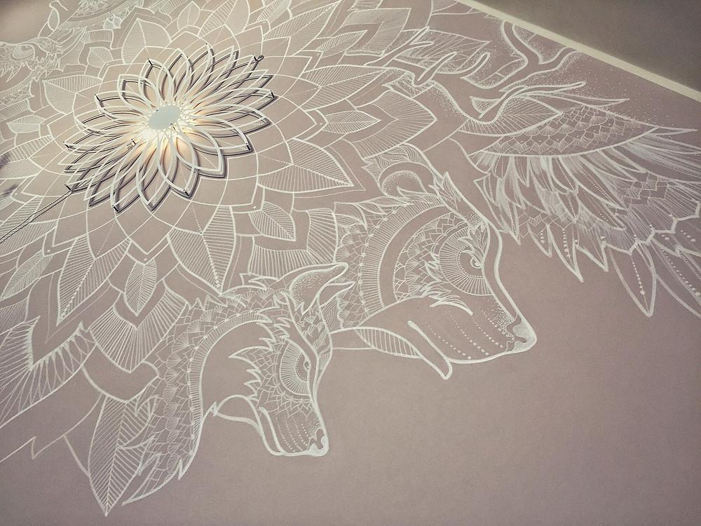 Sasha Luchkovan tekemä piirros, jossa keskellä lumpeenkukkaa muistuttavaa kuviota ja sivussa kaksi sudenkaltaisen eläimen päätä.