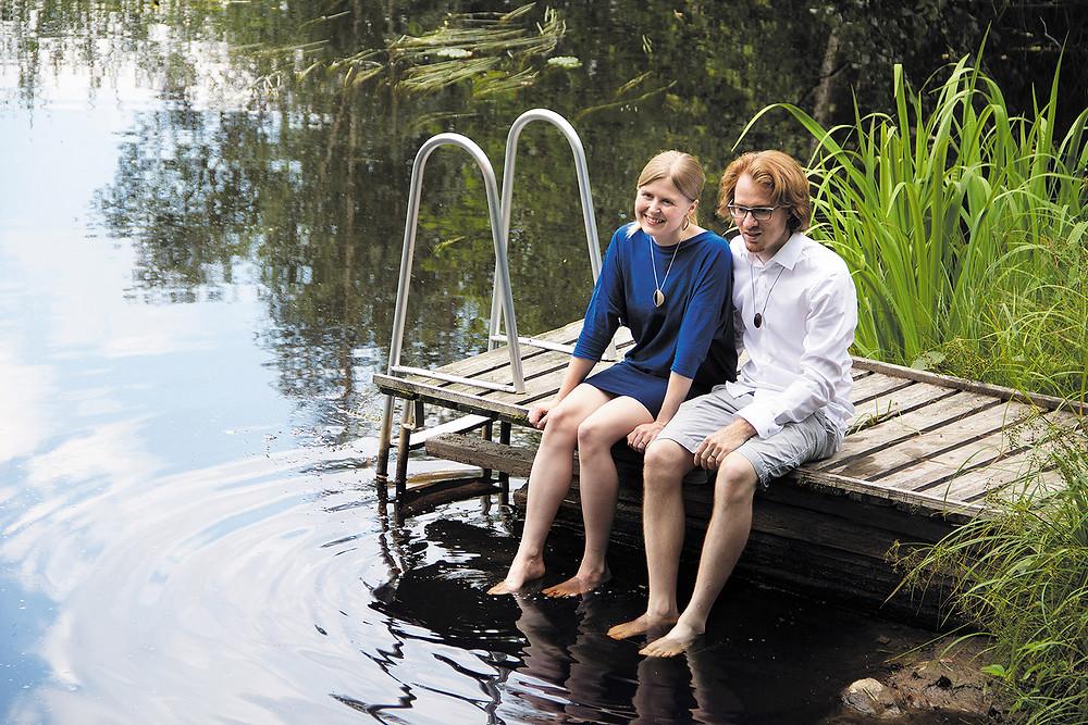 Susanna ja Tobias kesäisellä laiturilla, suomen suvessa, jalat tyynessä järvivedessä, iloisina