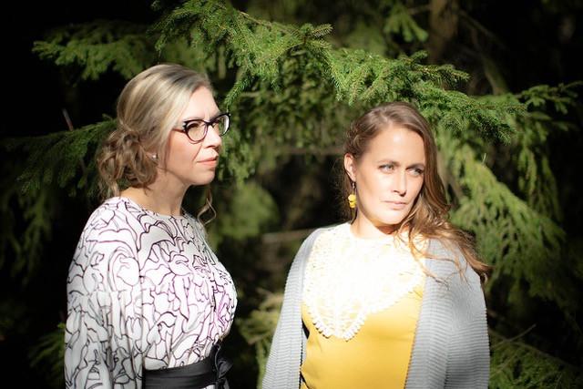 Elina Silvo ja Anna Karvosenoja kuvattuna kuusen edessä, taustalla näkyvät vain kuusen okset ja naiset katsovat poispäin kamerasta oikealle, ikään kuin toiseen kameraan.