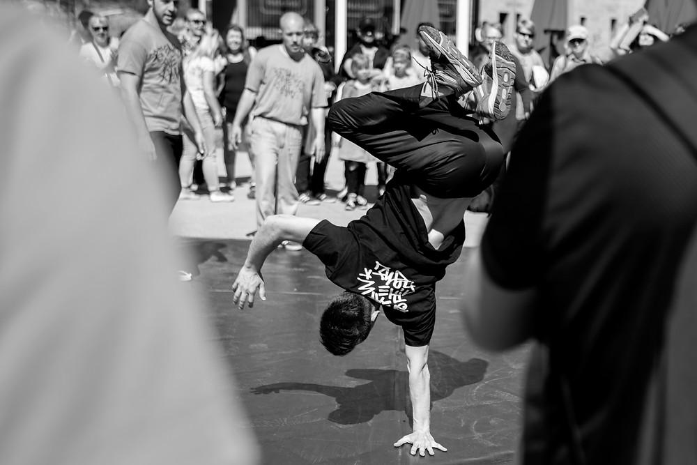 Breikkaaja Emre Sevim seisoo yhdellä kädellä ylösalaisin, jalat koukussa kohti taivasta