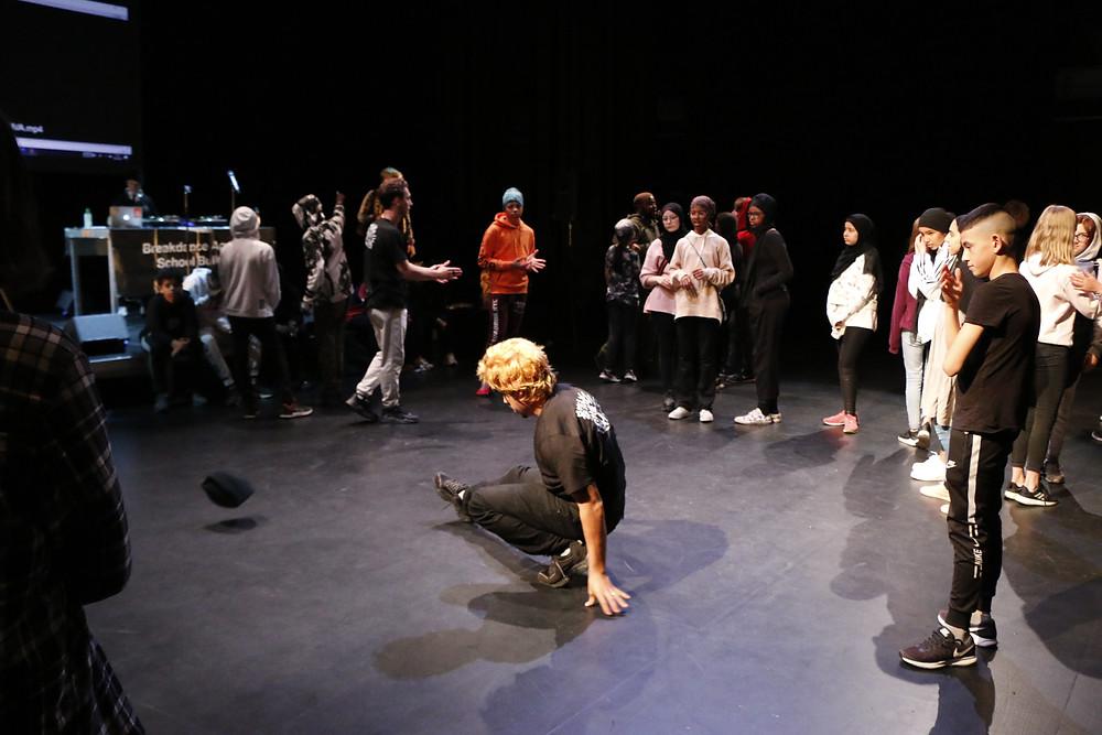 Kuvan keskellä lapsi breikkaa lattialla muiden, kymmenien lasten ja nuorten seuratessa ringissä hänen ympärillään.