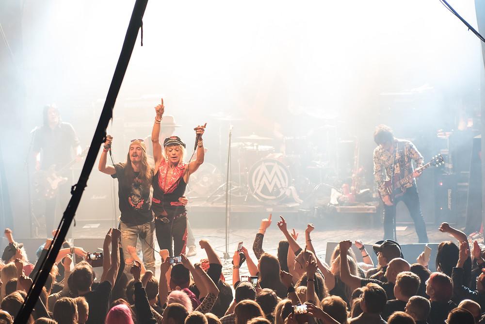 Andrea Brosio ja Michael Monroe keikalla kiittämässä yleisöä, taustalla muu bändi, kuvan edessä yleisöä hurraamassa