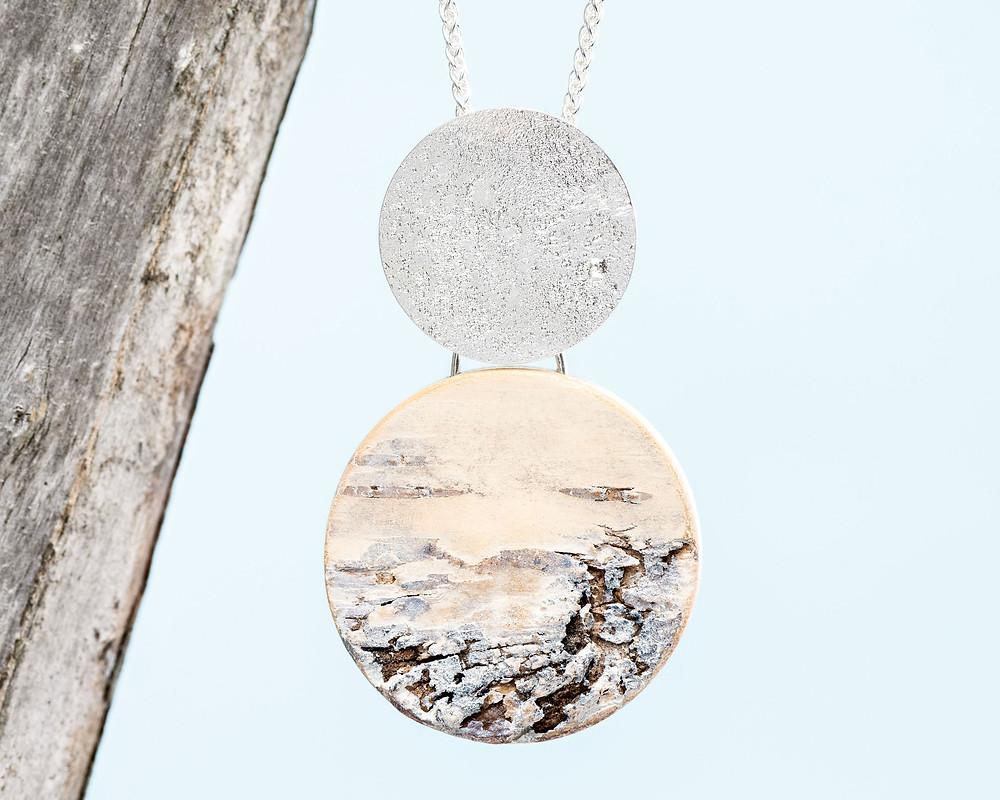 lähikuva kaulakorusta, jonka yläosassa hopeaa ja betoninomaista materiaalia, alaosassa suomalaista koivua