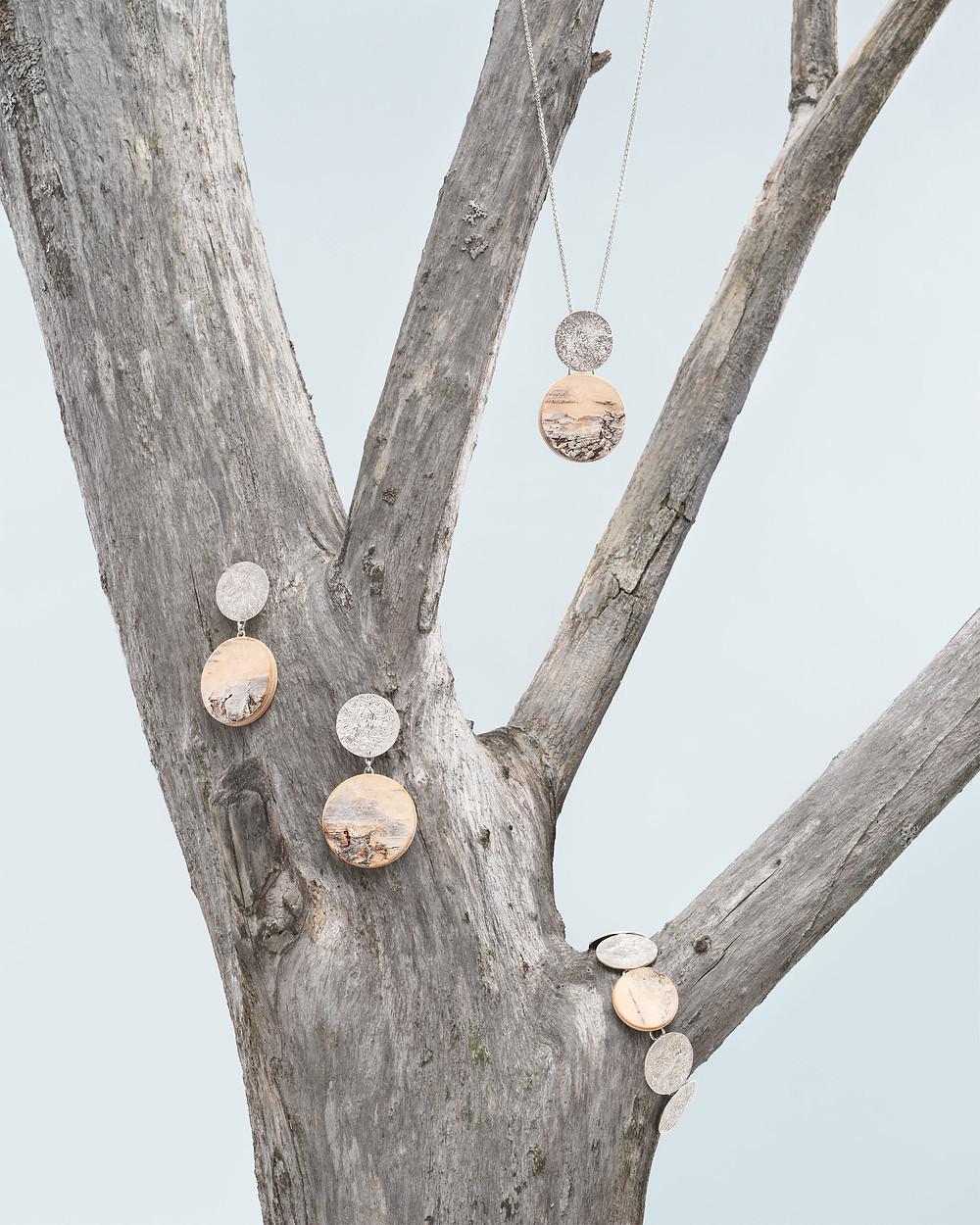 Vuoden koruksi valitun sarjan kaulakoru, rannerengas sekä korvakorut aseteltuna puunoksalle.