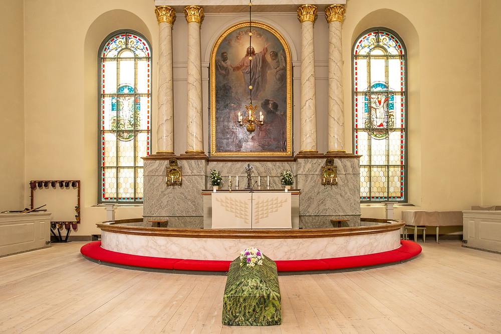 Arkku ja havu-arkkuliina kuvattuna kirkossa, alttarin edessä