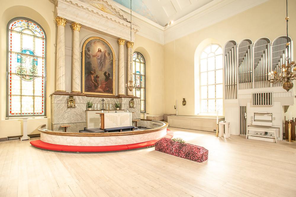 Arkku ja Paola Suhosen arkkuliina kuvattuna kirkossa. Liinan kuosin nimi on Ikuinen rakkaus.