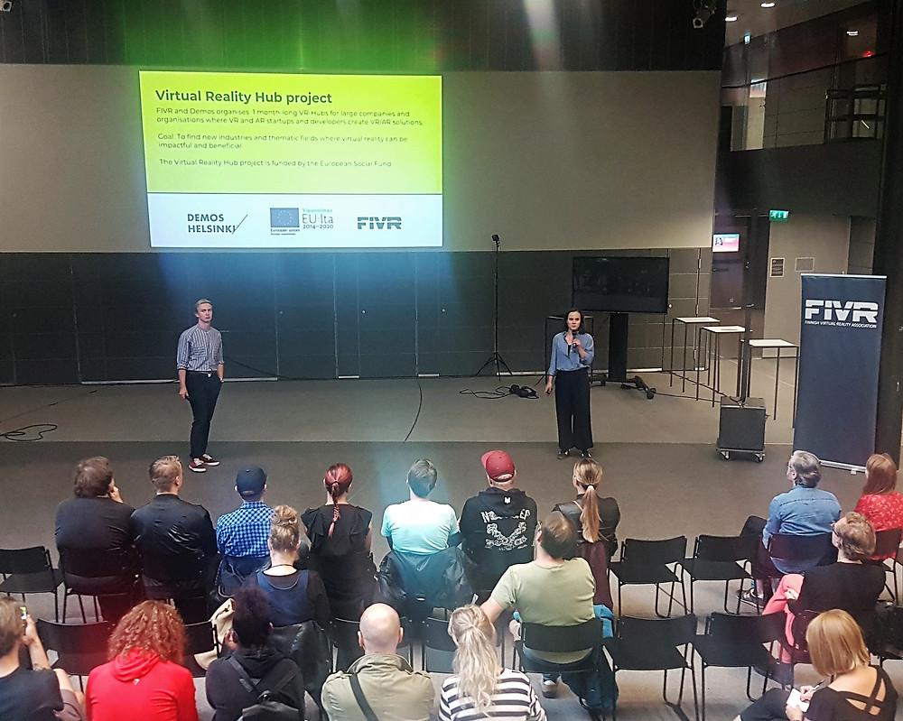 Santeri Suominen (FIVR) ja Leena Alanko (Demos Helsinki) esittelevät Virtual Reality Hub -projektia Taiteiden yön AR/VR Startups Meet the Cultural Scene -tapahtumassa Musiikkitalolla.