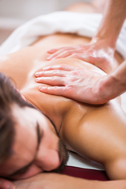 Young man is enjoying massage on spa tre