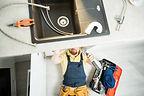 plumber-repairing-pipe-in-kitchen.jpg