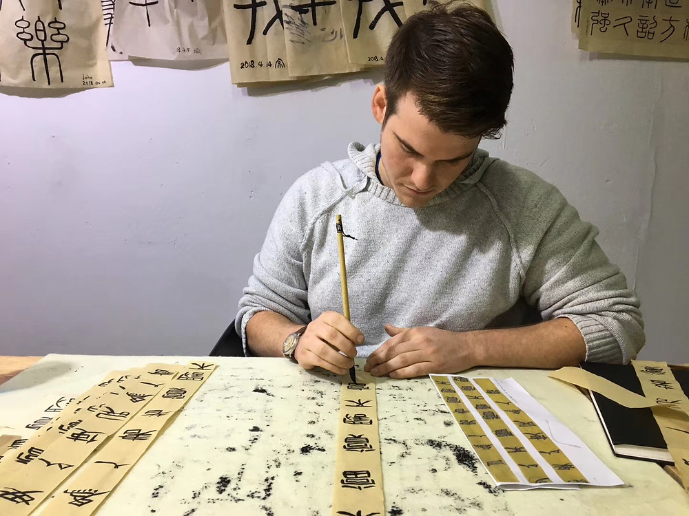 Practicing calligraphy after class at the residency.