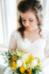 Bride looking down at her yellow and white flowers