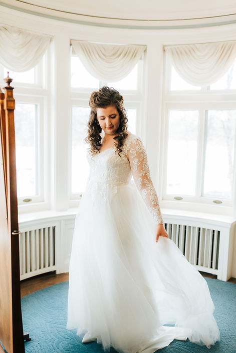 Bride standing in front of mirror with wedding dress at the Gale Mansion in Minneapolis Minnesota