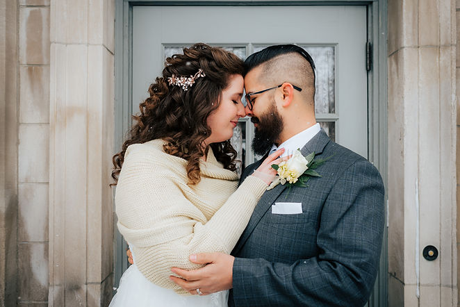 Bride and groom nose to nose with snow falling