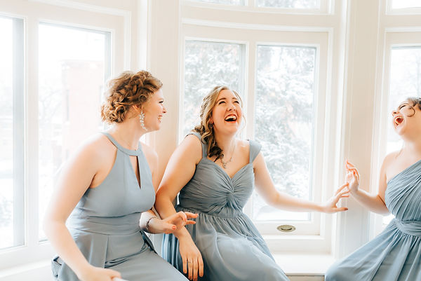 Bridesmaid in dusty blue dresses laughing in a window sill