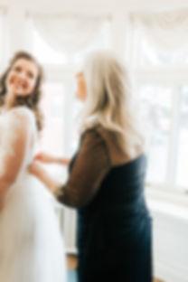 Mothe zips up bride's wedding dress at Gale Mansion