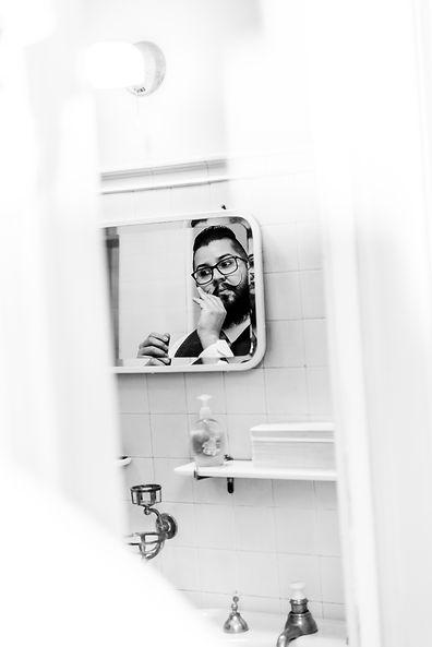 Groom molding his mustache in mirror
