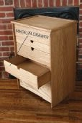 Wood sewing box depicting a medium size drawer.