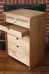 Wood sewing box depicting a small drawer.
