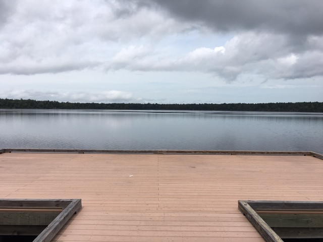panoramic view of an empty lake, fishing pier, treeline, cloudy sky