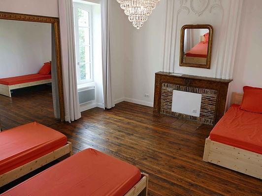 Grande chambre de trois lits avec moulures, grand lustre, cheminée en brique