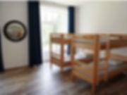 Grand dortoir lumineux avec 6 lits superposés donnant sur le jardin