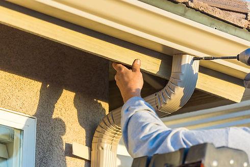 Worker Attaching Aluminum Rain Gutter an