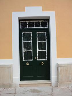 Puerta exterior doble con cristalera superior fija estilo menorquín lacada en verde