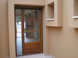 Puerta exterior cristalera con parte fija, lacada al natural