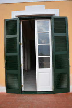 Puerta exterior blanca con persiana color verde Menorca