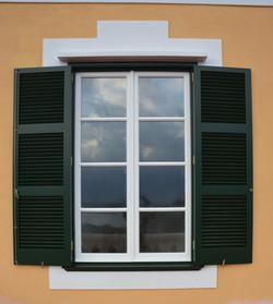 Ventana blanca tradicional con persianas color verde Menorca