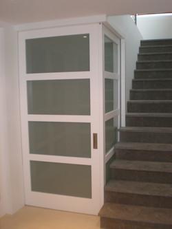 Puerta corredera doble en rincón con cristalera lacada en blanco
