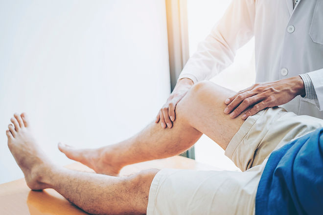 physician evaluating a patient's knee