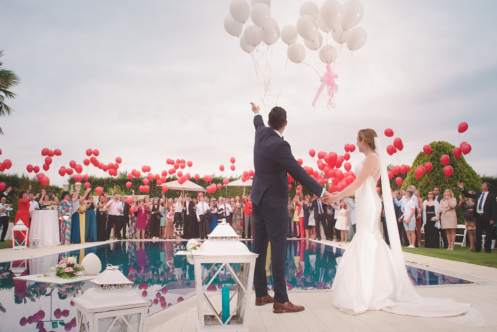 Bride, Groom and guests releasing balloons