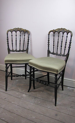Pair of ebonised and gilded side chairs.