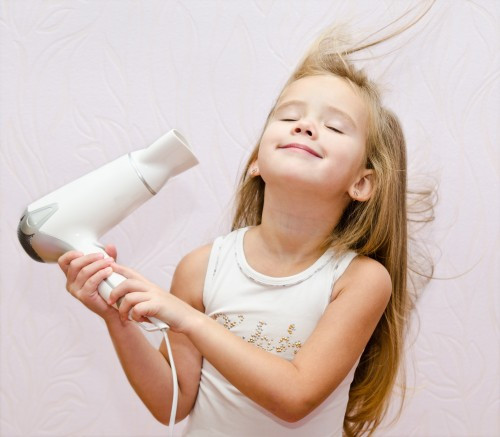 Cute smiling Little girl dries hair isolated