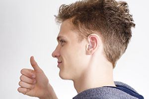 Teen with hearing aid showing thumb up, selective focus on ear