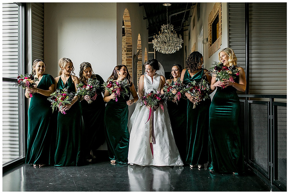 bride and bridesmaids in velvet green dresses with bouquets