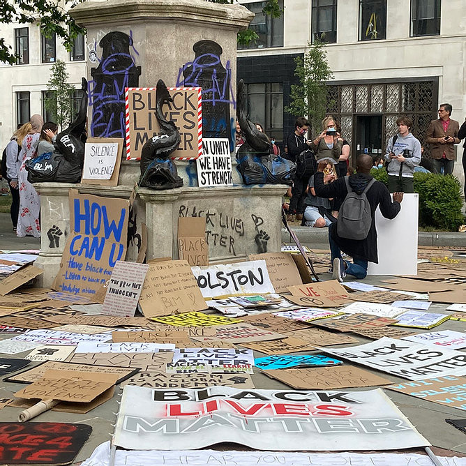 Black Lives Matter signs on the empty pedestal of the statue of Edward Colston in Bristol, which was toppled by protesters for honoring a slave trader (Image Source: Caitlin Hobbs, June 7th, 2020)