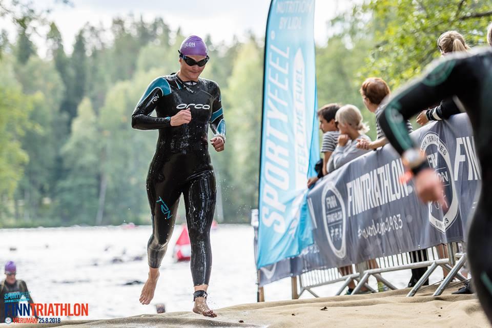 Joanna Rintala uintiosuudellaan lyhyellä juoksusiirtymällä järvestä toiseen.