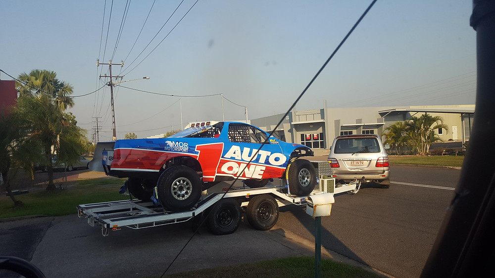 fully wrapped trophy truck on car trailer being towed.