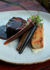 Filete de res en ceniza vegetal, pastel de papa, tocino y queso de oveja, zanahorias confitadas, salsa de reducción de vino tinto.