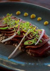 Tiradito de atún azul, salsa roja tatemada yuzu y crujiente de arroz.