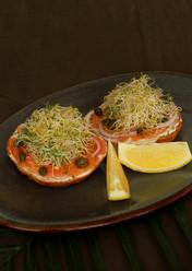 Bagel casero con salmón curado en casa, queso crema, alcaparras y cebolla morada