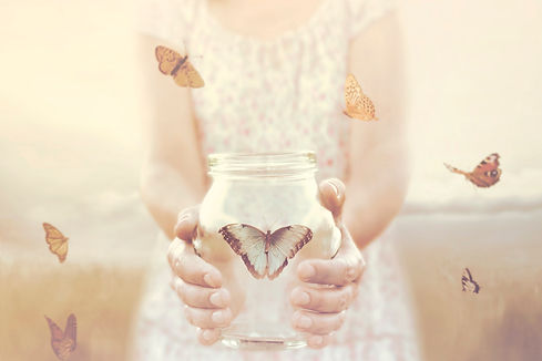 woman gives freedom to some butterflies enclosed in a glass vase.jpg