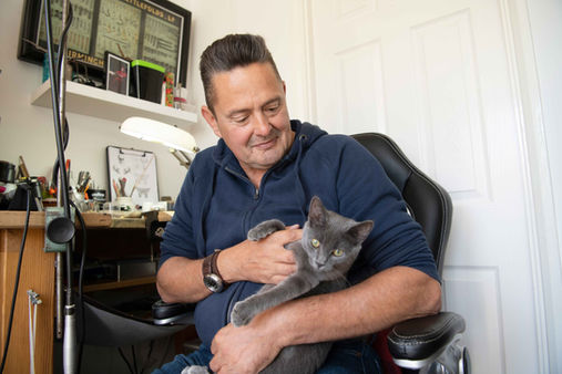 Steve-holding-his-grey-cat, a patient after treatment